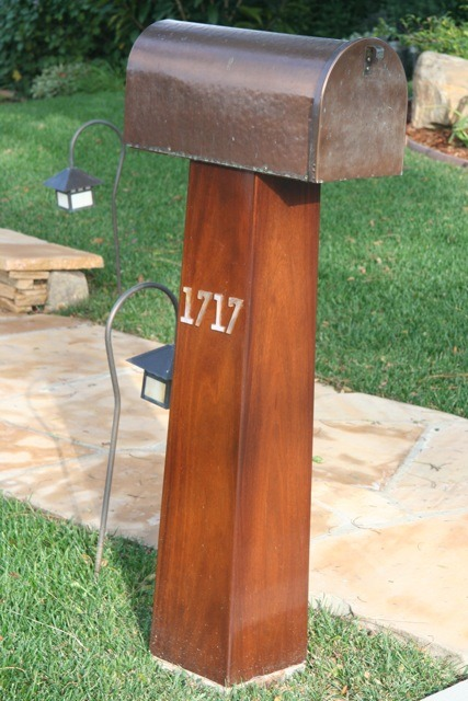 This mailbox is hand-hammered copper sitting atop a Honduran mahogany, tapered post. The taper matches the same tapered angles as the columns on the house. I could not find numbers that would contrast with the dark post so I made these out of iridescent glass with a copper foiled border.