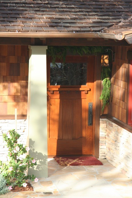 The tapered column matches the mailbox taper. Copper gutters and a copper peacock sconce add to the Craftsman feel. The front door is solid mahogany and weighs in at 150 pounds with a stained glass window I made myself.