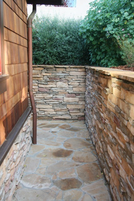 This entire walkway around the garage was built using Golden Buckskin flagstone for the walkway and cultured stone for the wall.