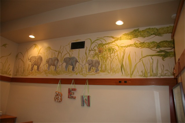 This view of Margit Wypyszyk's mural shows elephants in a line with a cheetah peering through the grass. The entire mural only took two days.