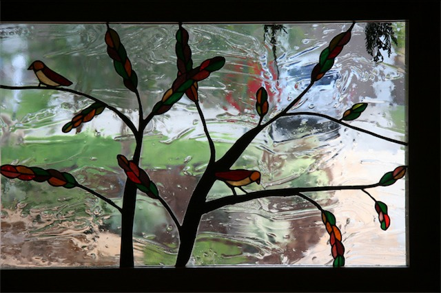 I made the stained glass window after living in the house about a year (Amy sketched the birds). We wanted to see who was at the door without people seeing in from the street so I used a seeded, wavy, clear glass. The tree trunk is solder that is layered to look like bark. The leaves were designed to match the living room wall sconces in which I also did the glass.