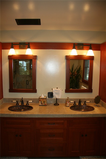 The countertop is Seagrass limestone. The sinks are hand-hammered copper sinks from Mexico. The fixtures are oil-rubbed bronze with Carrara marble handles. <br />To keep within the wood palette and overall feel, the two mirrors are mahogany with ebony accents.