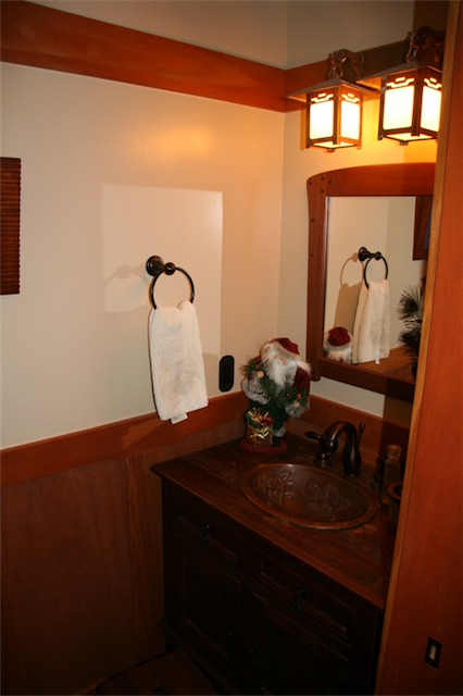 The lights were found at Old California Lantern, the mirror is mahogany with ebony plugs, the sink is hand-hammered copper, and the vanity is mesquite.