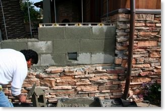 The stone veneer of the house will blend into the barbecue island